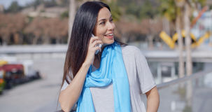 Enthusiastic female using phone outdoors Stock Images