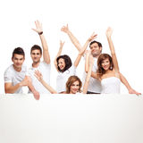 Enthusiastic friends advertising white board. Group of smiling friends excited over a white banner Stock Photo