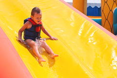 Enthusiastic kid on slide Royalty Free Stock Photos