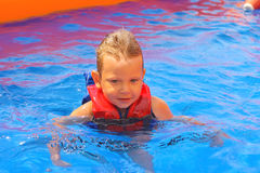 Enthusiastic kid in vest at the pool. Kid in vest at the pool water park stock photo