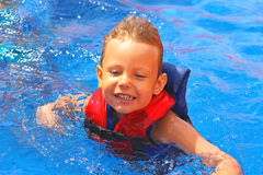 Enthusiastic kid in vest at the pool. Water park stock images