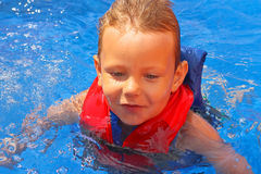 Enthusiastic kid in vest at the pool Stock Photography