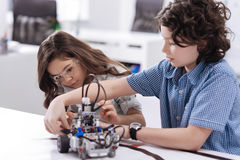 Enthusiastic kids enjoying science class at school. Enjoying our science adventure. Skilled resourceful genius kids sitting at school and creating robot while Royalty Free Stock Photography
