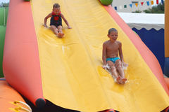 Enthusiastic kids on slide Royalty Free Stock Photography