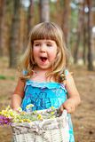 Enthusiastic little girl holding a basket of flowers in the fore Royalty Free Stock Photos