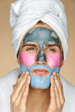 Enthusiastic man applies a face mask. Photo of man in towel with different face masks on his face. Beauty & Skin care concept Royalty Free Stock Images