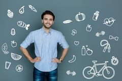 Enthusiastic man looking happy while leading a healthy lifestyle. Healthy lifestyle. Cheerful slim young man feeling good while leading a healthy lifestyle Royalty Free Stock Photography