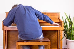 Enthusiastic man playing the piano with gusto Stock Photography