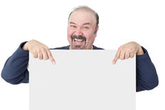 Enthusiastic man pointing to a blank white sign. Enthusiastic middle-aged man with a goatee laughing and pointing to a blank white sign he is holding ing front stock photo