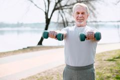 Enthusiastic mature man training with dumbbells Royalty Free Stock Image