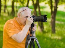 Enthusiastic mature photographer. Taking professional photo outdoor Stock Photography