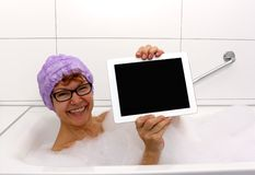 Enthusiastic mature woman in bathtub with tablet computers Royalty Free Stock Image