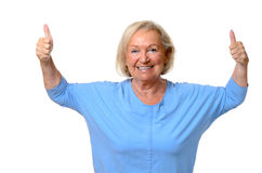 Enthusiastic motivated senior woman. With a beaming smile giving a double thumbs up gesture to show her approval and success,upper body isolated on white stock images