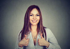 Enthusiastic motivated woman giving a thumbs up gesture of approval. And success on gray background stock photo