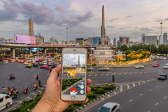 Enthusiastic Pokemon player is catching Magikarp at Victory Monument Royalty Free Stock Photo