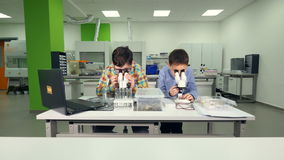 Enthusiastic school boys doing science experiment in school laboratory. stock video