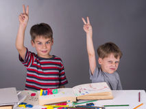 Enthusiastic schoolboys raising their hands to give an answer, education concept Royalty Free Stock Images