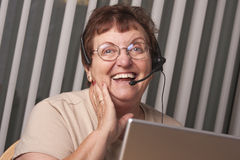 Enthusiastic Senior Adult Woman with Telephone Headset and Monitor Royalty Free Stock Photography