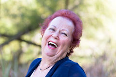 Enthusiastic Senior Woman Giving a Genuine Laugh. Red hair enthusiastic senior woman giving a genuine laugh Royalty Free Stock Photography