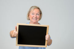 Enthusiastic senior woman holding a blackboard. Enthusiastic elderly woman with a blank blackboard or slate that she is holding in front of her chest with a royalty free stock image