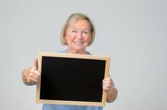 Enthusiastic senior woman holding a blackboard Royalty Free Stock Image