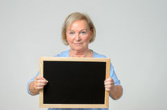 Enthusiastic senior woman holding a blackboard. Serious elderly woman with a blank blackboard or slate that she is holding in front of her chest, copyspace for royalty free stock photography