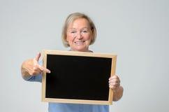 Enthusiastic senior woman pointing to a blackboard Royalty Free Stock Photos