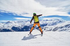 Free Enthusiastic Skier Wearing Colorful Clothes And A Green Backpack, Posing On A Ski Slope In Les Sybelles Ski Resort. Stock Images - 168880184