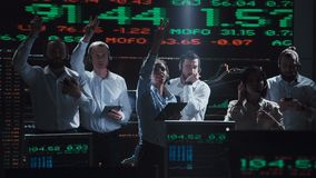 Enthusiastic stock broker team in live office. An enthusiastic stock broker team in a futuristic office full of live global market feeds stock video footage