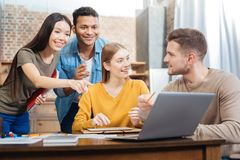 Enthusiastic students looking at the screen while generating wonderful ideas. Great idea. Positive emotional students smiling and feeling excited while pointing royalty free stock photography