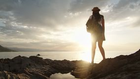 Enthusiastic travel backpacker female admiring amazing sunset having positive emotion. Full shot. Back view independent woman tourist relaxing looking on stock video footage