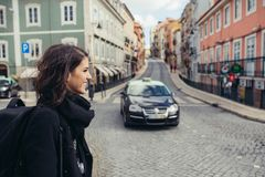 Enthusiastic traveler woman walking streets of european capital.Tourist in Lisbon,Portugal. Narrow, colorful,charming streets inviting curious woman tourist royalty free stock image