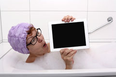 Enthusiastic woman in bathtub with tablet computers Royalty Free Stock Photography