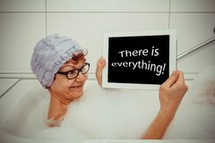 Enthusiastic woman in bathtub tablet computers Stock Photography
