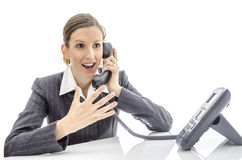 Enthusiastic woman talking on the phone. Enthusiastic woman at office desk talking on the phone.  on a white background Royalty Free Stock Photography