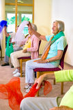 Enthusiastic women doing exercises in chairs. Stock Images