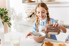 Enthusiastic young girl preparing herself nutritious breakfast Royalty Free Stock Image