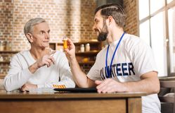 Enthusiastic young man recommending wonderful vitamins to an old man Stock Image