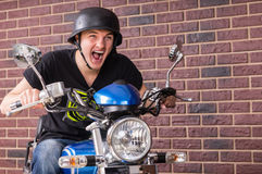 Enthusiastic young man riding his motorbike. Shouting as he speeds along in front of a brick wall in a retro helmet Royalty Free Stock Photography