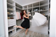 Enthusiastic young woman jumping in dressing room, nice wardrobe with skirt in hands. She`s happy with the choice. She`s. Dressed in black dress and silver royalty free stock images