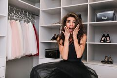 Enthusiastic young woman stands in the closet and jumps. Her dress hovers in the air, she looks into the camera, on the. Face wow emotions, in shock, surprise royalty free stock photo