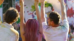 Enthusiastic youth raising hands in crowd, enjoying Holi color festival outdoors stock video footage