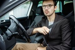 Enthusiastical young guy clips on his belt. He is sitting at his car. Road safety concept.  stock images