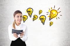 Enthusiastische Frau mit einem Planer, Glühlampen Lizenzfreie Stockbilder