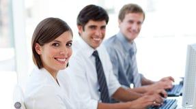 Enthusiastische Geschäftsleute, die an den Computern arbeiten Lizenzfreies Stockfoto