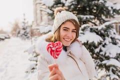 Enthusiastische kaukasische Frau, die Herzlutscher während Winter photoshoot hält Frohes Mädchen trägt Strickmütze und weißen Man lizenzfreie stockbilder