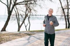Enthusiastischer älterer Mann, der in Park schlendert stockfotos