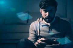 Enthusiastischer Mann, der Konsole zu Hause spielend verwendet Lizenzfreies Stockfoto