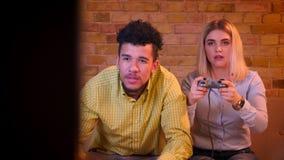 Enthusiastisches multinationales Paarspielvideospiel mit dem Steuerknüppel, der glücklich und im gemütlichen Haus aufmerksam ist stock video footage
