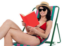 Enticing bikini model on a deckchair reading a book Royalty Free Stock Image